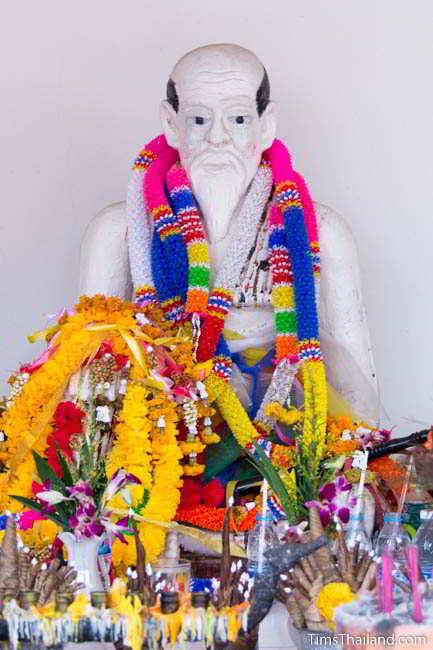 Statue of man covered in garlands at fifth Khon Kaen city pillar shrine, at Ban Thum