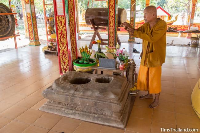 thai buddhist monk standing next to sandstone pedestal of Ku Bueng Jiew Khmer ruin