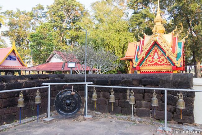 Bells and gone alongside laterite enclosure at Ku Sunthararam Khmer Ruin