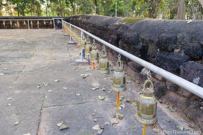 Bells alongside laterite enclosure at Ku Sunthararam Khmer Ruin