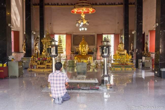 man praying before Luang Por Phra Phut Buddha image
