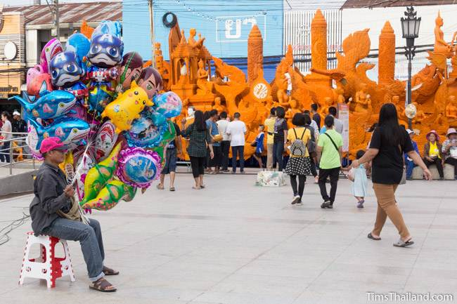 man selling balloons next to Khao Phansa candle parade float