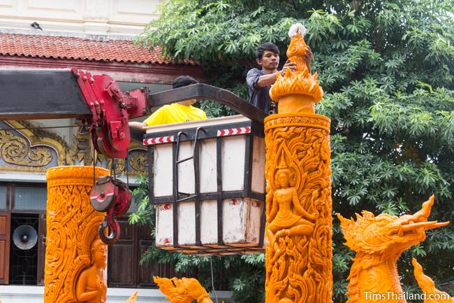 two men in a crane putting the top on a Khao Phansa candle parade float