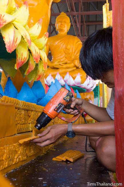 man using heat gun to make a Khao Phansa candle parade float