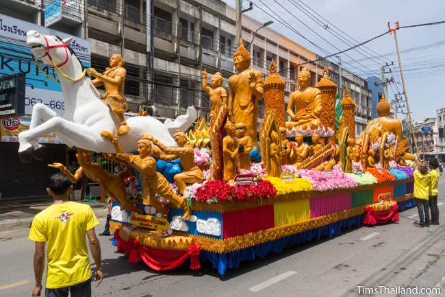 Khao Phansa candle parade float with a white horse driving down the street