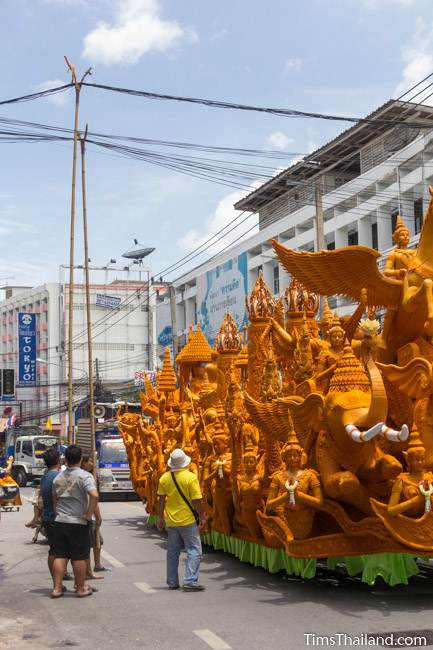men lifting power lines over a Khao Phansa candle parade float driving down the street