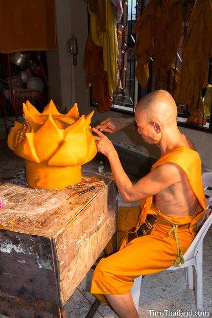 monk carving a part of a Khao Phansa candle parade float