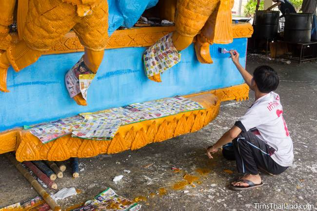 man painting blue wax on a Khao Phansa candle parade float