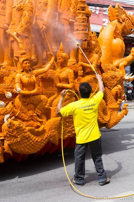 man spraying water on a Khao Phansa candle parade float
