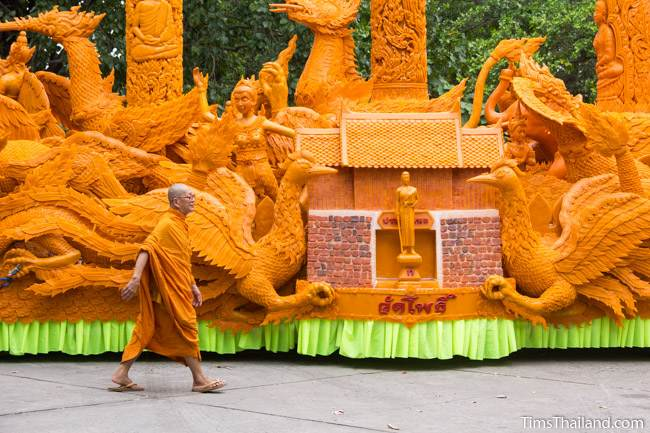 monk walking on front of a Khao Phansa candle parade float with the Thao Suranari Monument and Chumphon Gate on it