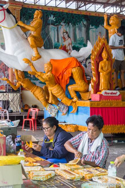 women carving wax pieces for a Khao Phansa candle parade float