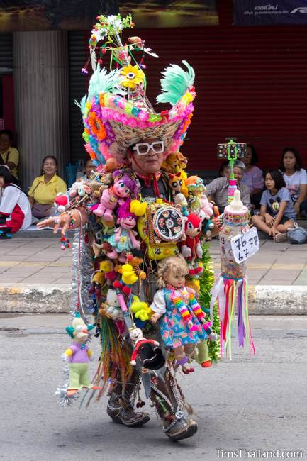 man wearing suit made of dolls in Khao Phansa candle parade