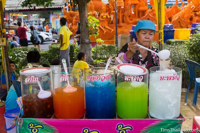 woman selling drinks in front of a Khao Phansa candle parade float