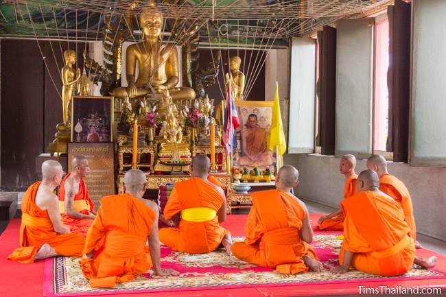 monks in front of a large Buddha