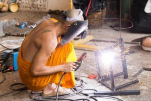 monk welding for making a Khao Phansa candle parade float