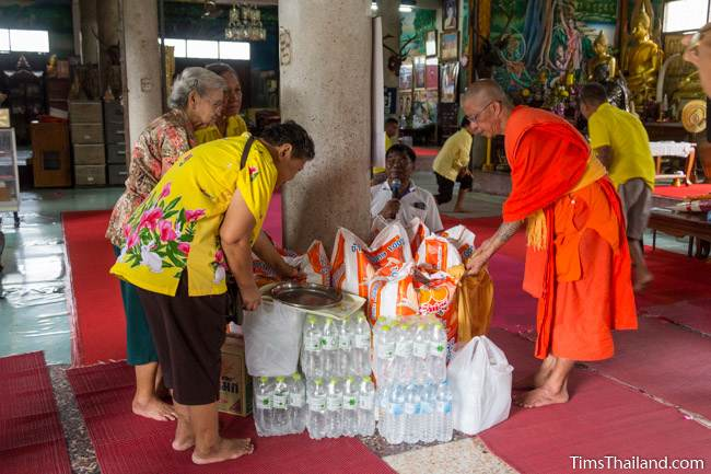 people making offerings to a monk