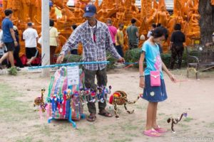 man selling puppets in front of a Khao Phansa candle parade float