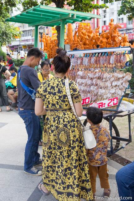 man selling dried squid in front of a Khao Phansa candle parade float