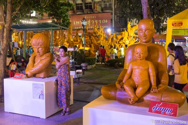 wax sculptures in front of a Khao Phansa candle parade float