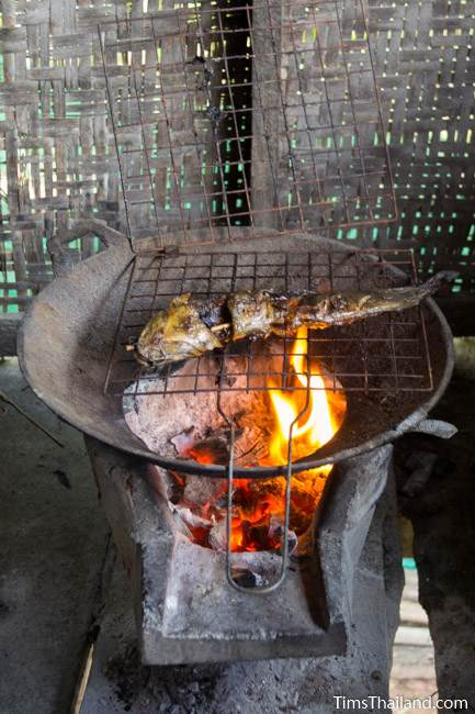 fish cooking on a charcoal grill