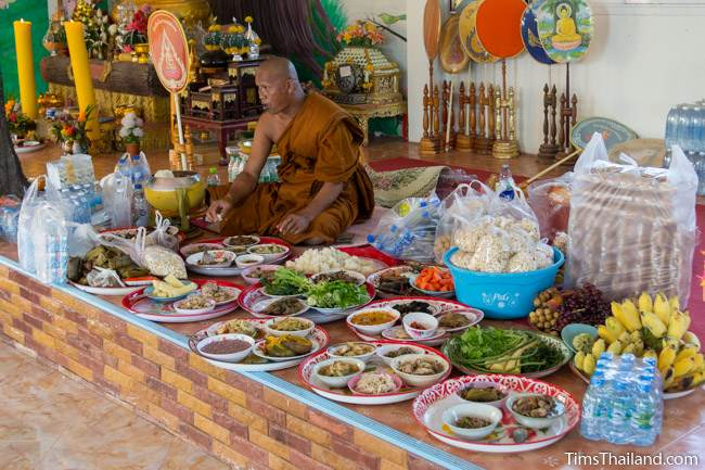 monk eating with many food trays next to him