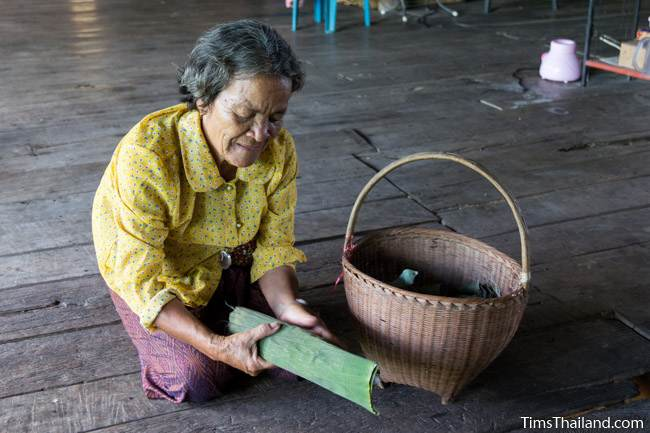 woman wrapping fish in a banana leaf