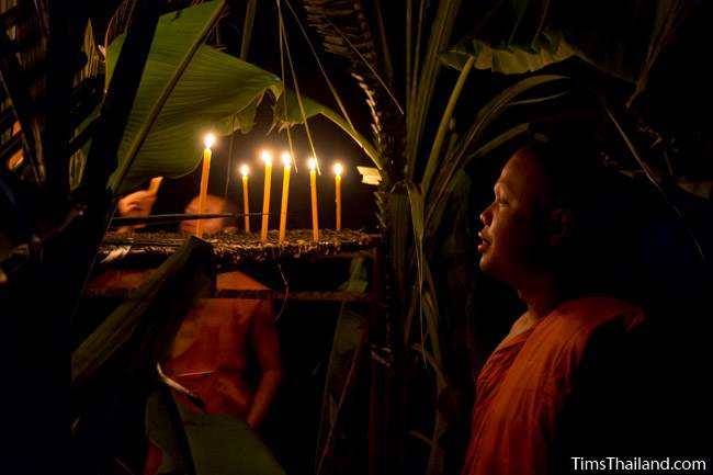 monk lighting candles during Ok Phansa