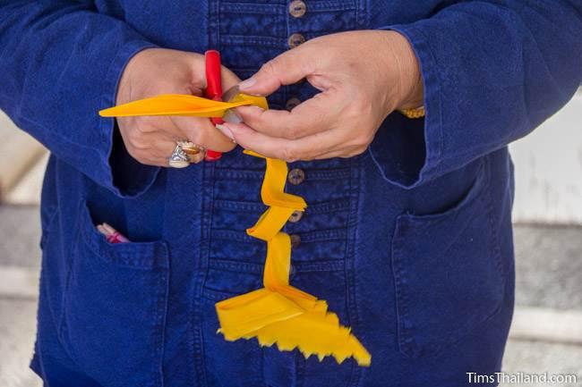woman cutting paper to make lantern for Kathin celebration