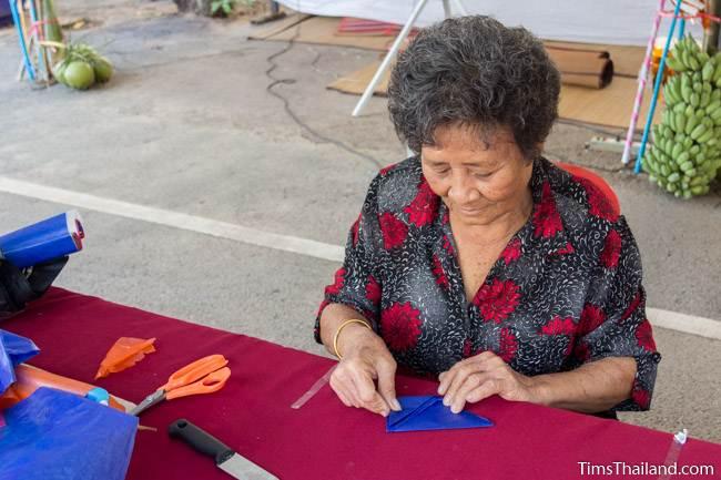 woman folding paper to make lantern for Kathin celebration