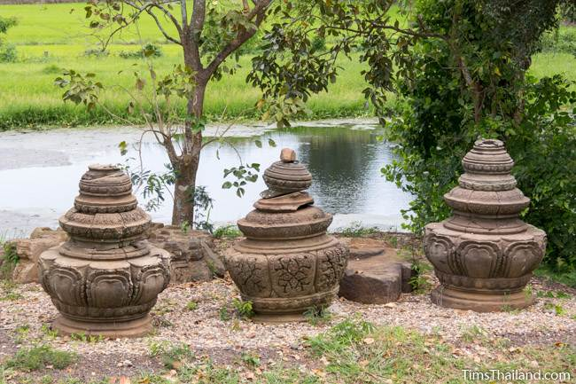 three lotus-bud tops at Prang Phakho Khmer ruin with moat in background
