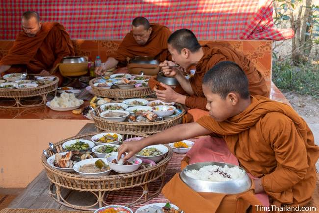 monks eating off of big trays at Boon Berk Bahn
