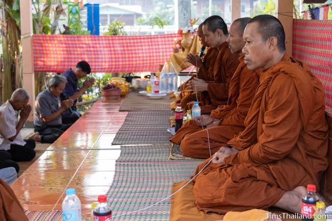 monks holding sacred thread at Boon Berk Bahn