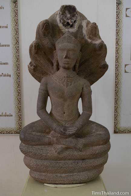 Buddha meditating under a naga stone carved statue