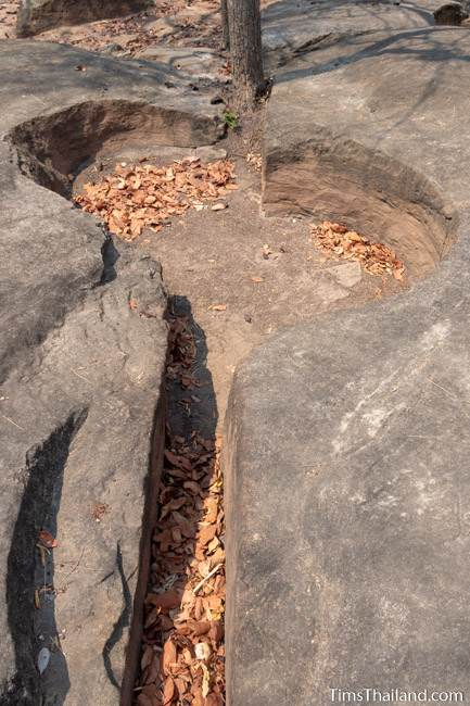 natural split in the sandstone and a pothole