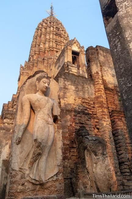 Sukhothai-style walking Buddha in front of prang