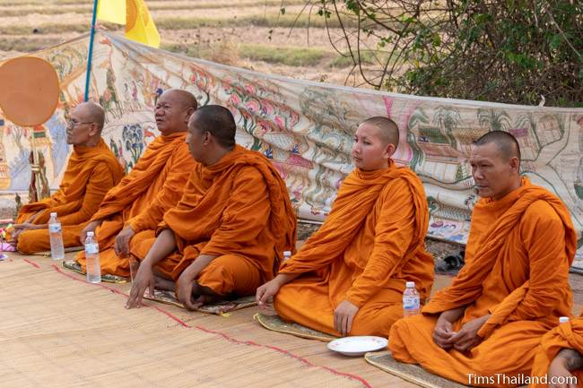 monks sitting in front of Pha Wet banner