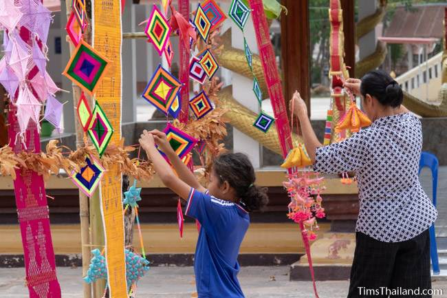 woman and girl hanging decorations outside wihan