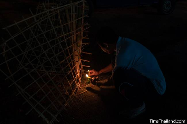man lighting a candle in the dark