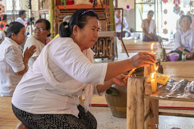 woman lighting a candle in the wihan