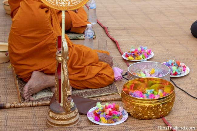 bowls of coins next to a monk