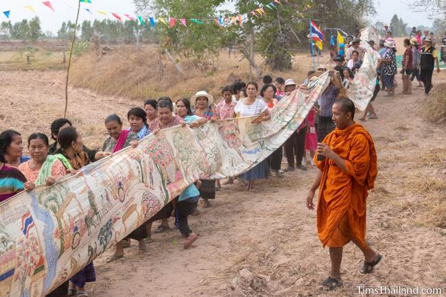 people carrying Pha Wet banner through a rice field