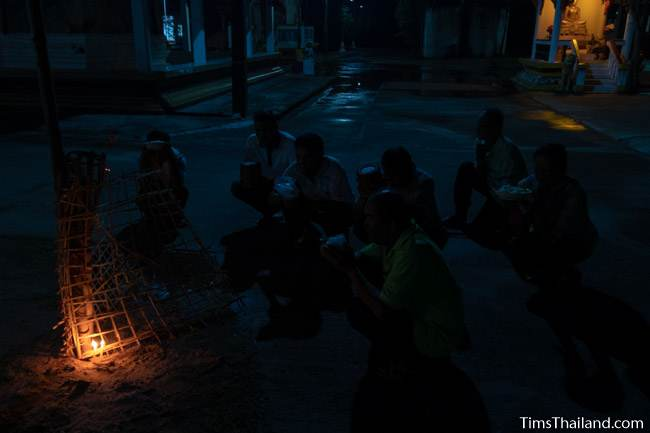 people praying at night in front of a candle