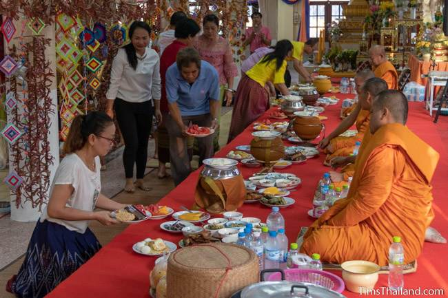 people serving food to monks