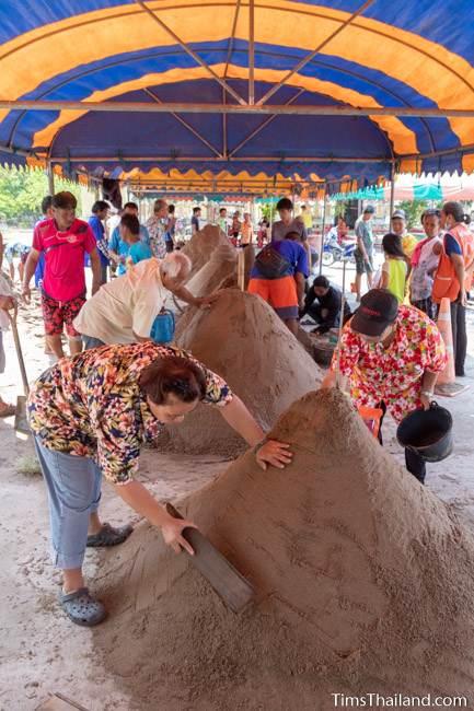 people building sand stupas