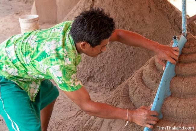 using template to shape sand on a sand stupa