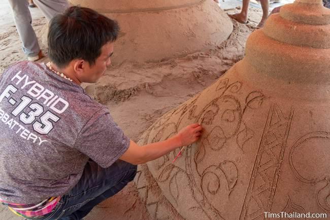 man carving design into sand stupa