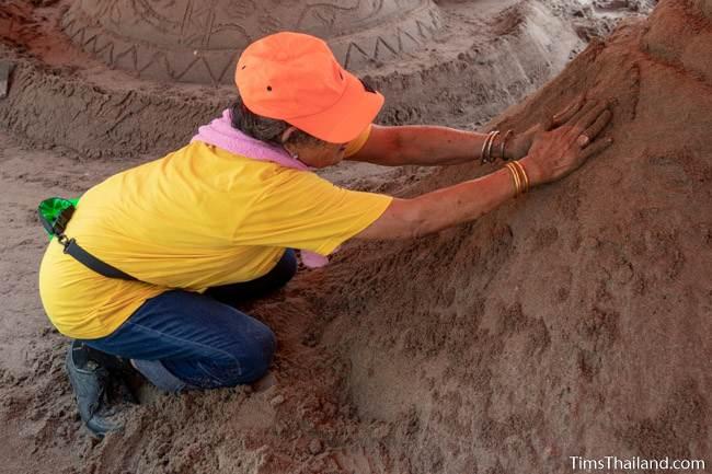 patting down sand on a sand stupa