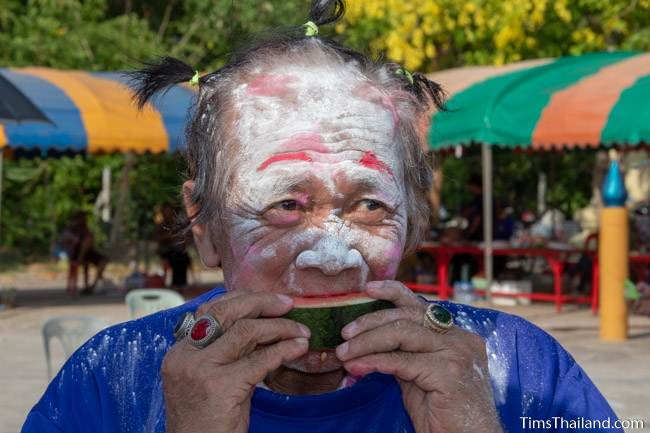 man with face painted eating watermelon