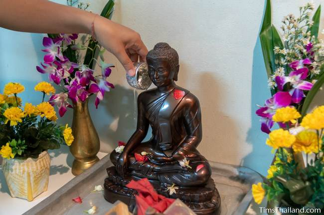 pouring water on Buddha at a house