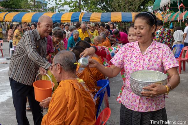 men and women pouring water on monks